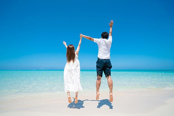 砂浜でジャンプするカップル